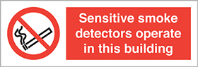 Sensitive smoke detectors operate in this building label. sign